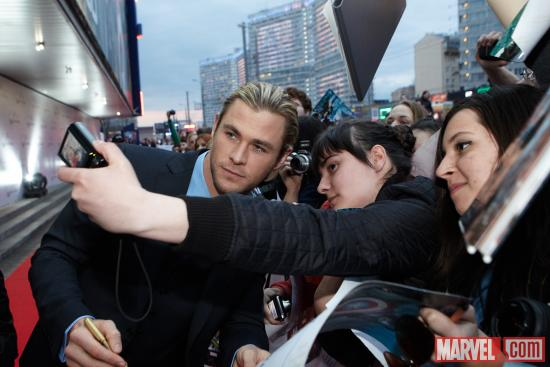 Chris Hemsworth takes photos with fans at the Moscow premiere of Marvel's The Avengers